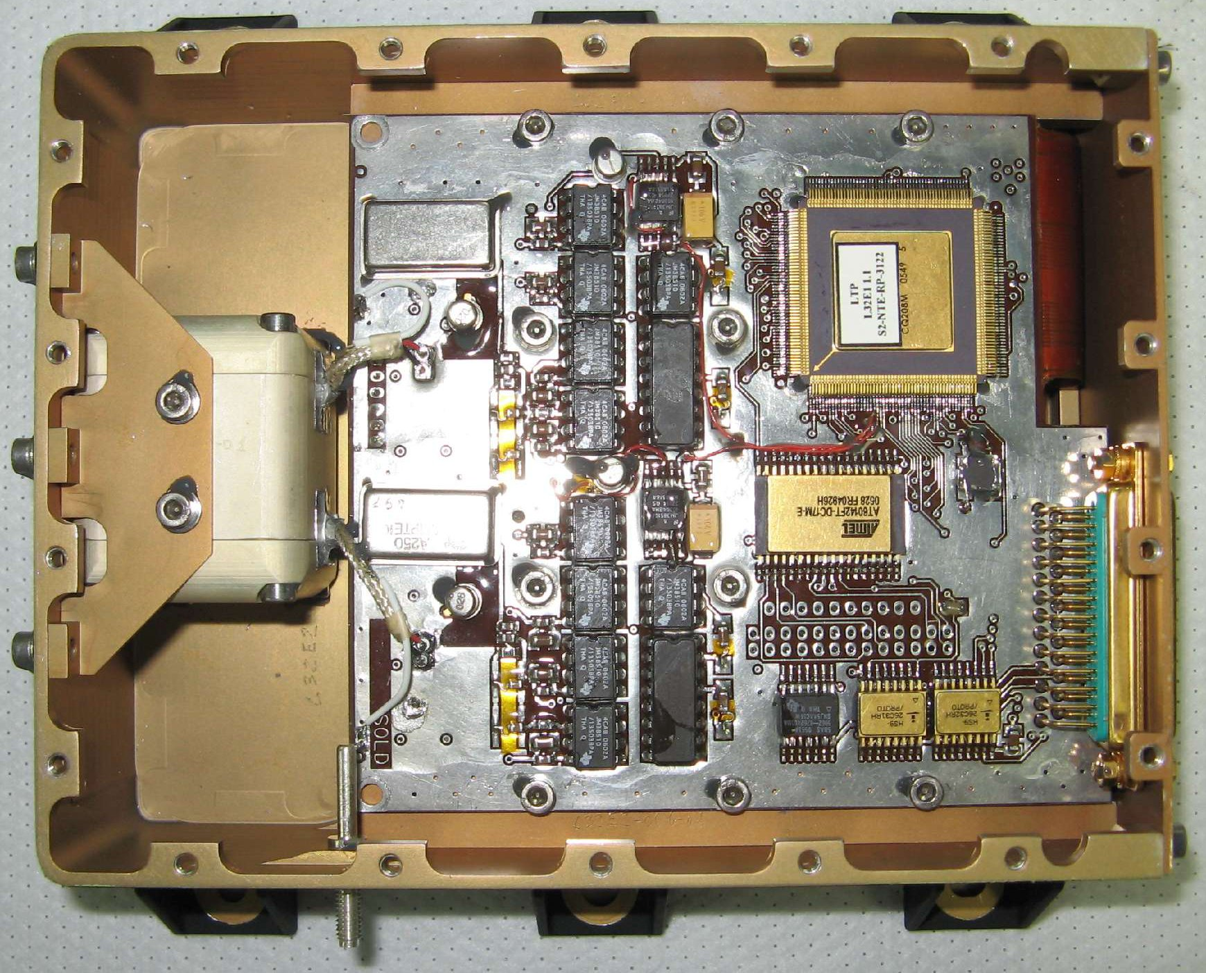 Left: A top-down photograph of the radiation monitor, with the lid removed. The cubic copper shield can be seen on the left, next to the unit's electronics. Right: A production photograph of one of the flight PIN diodes mounted on the wall of its copper shield. Note only the larger black region was sensitive and the