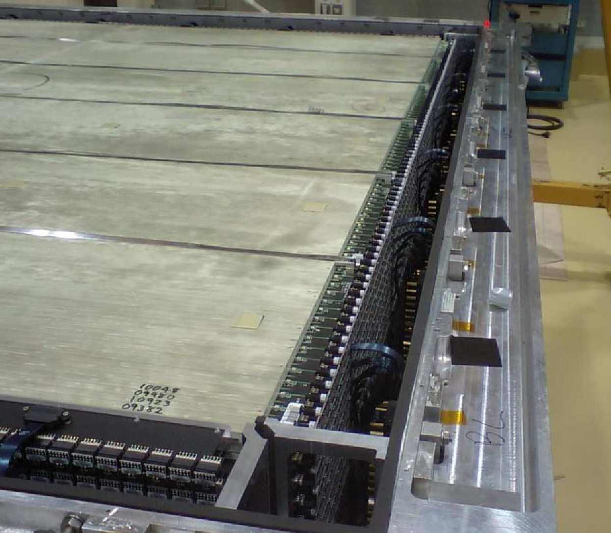 Photograph of the XY modules inside the dark box. Busboards carrying photosensors are mounted along all four sides of each module. Ribbon cables connect each busboard to the backplanes (not visible in this photo) on the sides of the dark box. Angular support brackets in the corners of the dark box (bottom center of photo) prevent lateral movement of the XY modules within the dark box. The five stainless steel straps are also visible.