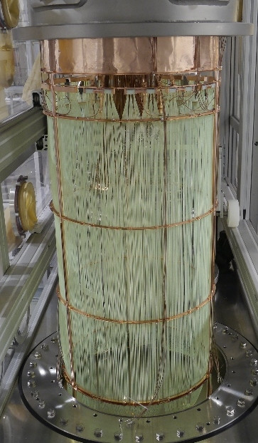 Photos of the liquid argon veto system. Left: fiber curtain with SiPM readout at the top. Right: top and bottom arrangement of PMTs.